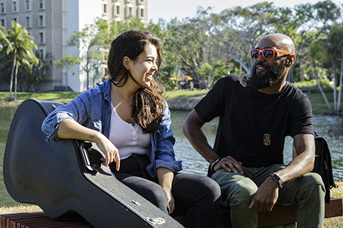 Two students relaxing during a break by Lake Osceola at the University of Miami Coral Gables campus